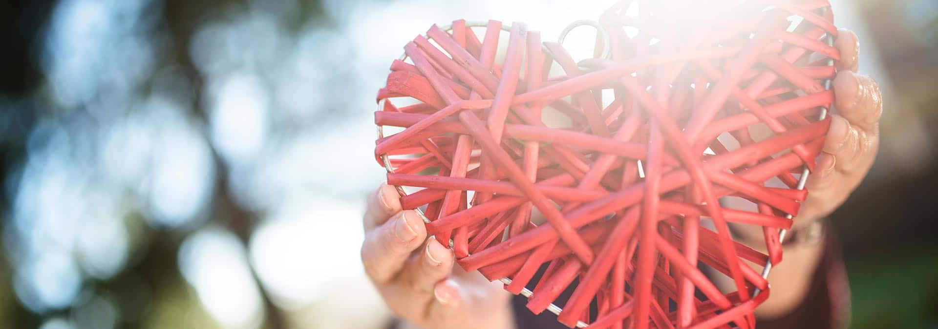 Red wicker heart held up by person.