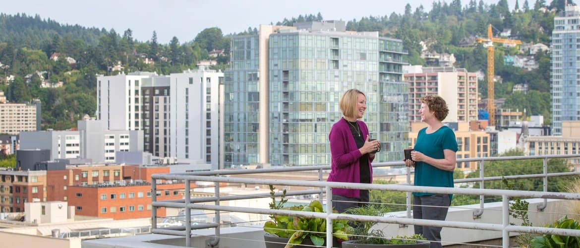 Two female attorneys talking on a roof deck in front of a city skyline.